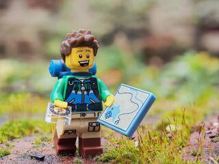 bildet viser en blid LEGO-mann med kart, kompass og ryggsekk