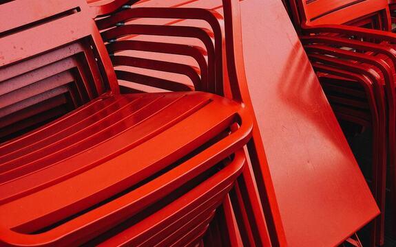 Foto av en stabel med røde stoler og bord