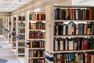 bildet viser en rad hvite bokhyller med bøker i forskjellige farger