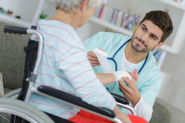 Mann sykepleier - bandasjerer hånd