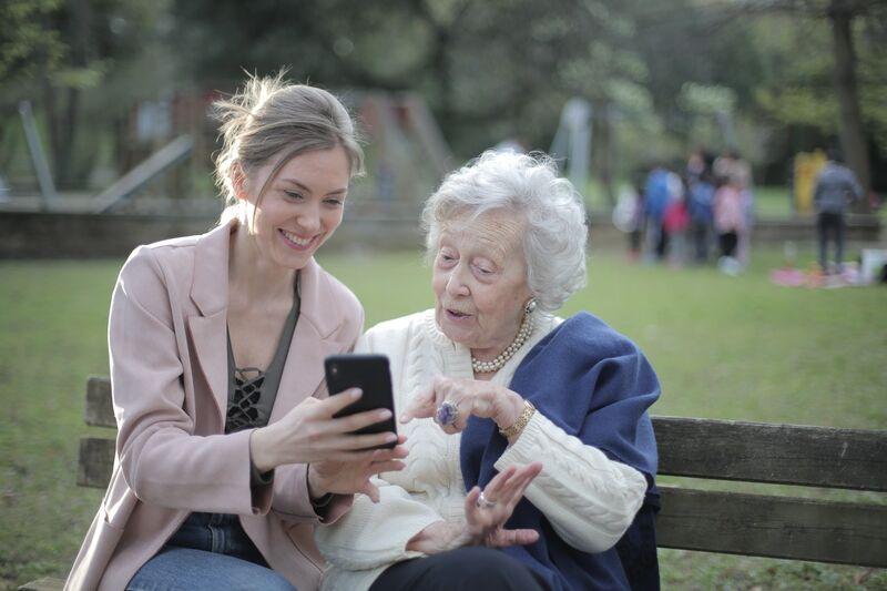 ung kvinne viser eldre kvinne noe på mobil