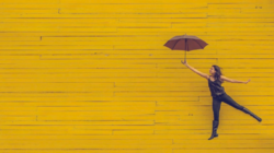 kvinne på ett ben med paraply gul bakgrunn