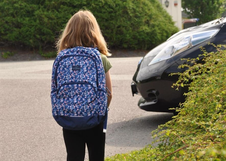 Ei jente går bortover veien, med en høy hekk på ene siden. En bil er på vei ut fra en gårdsplass.