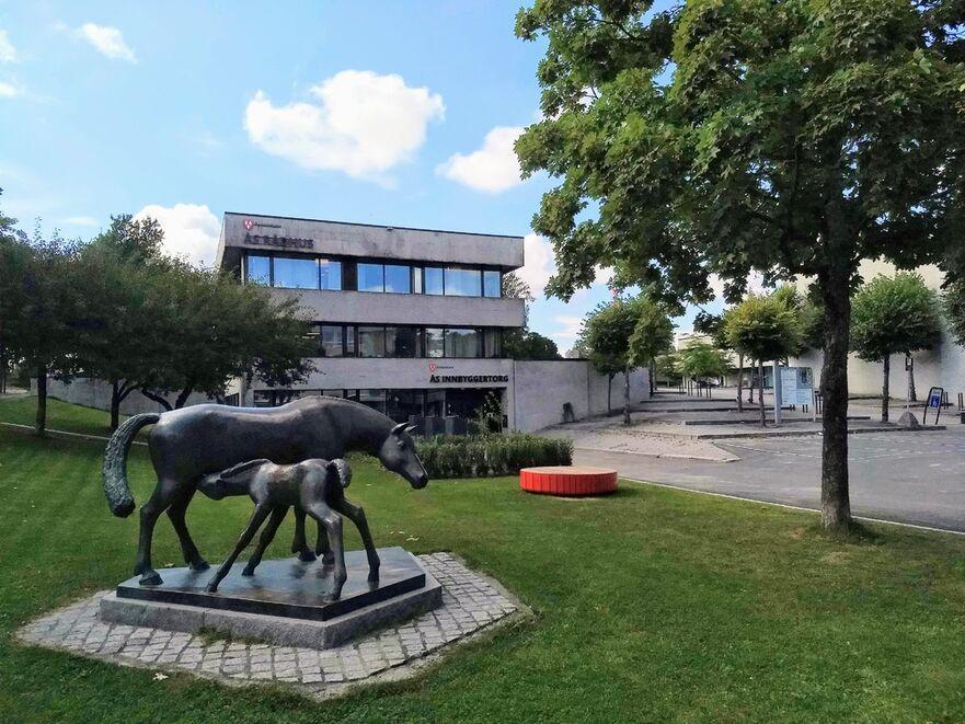 Oversiktsbilde av fasaden til Ås innbyggertorg, med statuen Hoppe og føll i forkant.