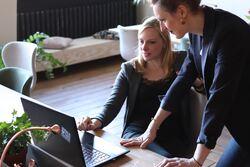 To kvinner som samarbeider ved en skjerm, en står.