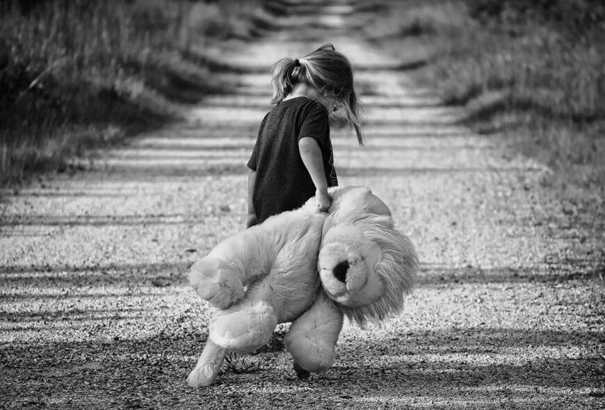 Jente som holder en stor bamse og går langs en veo
