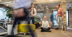 utydelige mennesker i kontormiljø farer forbi. kvinne sitter på gulvet i lotusstilling for meditasjon