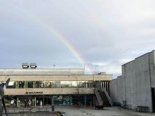 Foto av fasaden på Ås kulturhus med en regnbue over