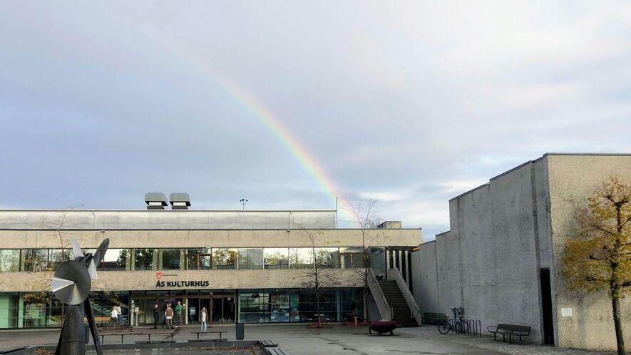 Foto av Ås kulturhus med regnbue over