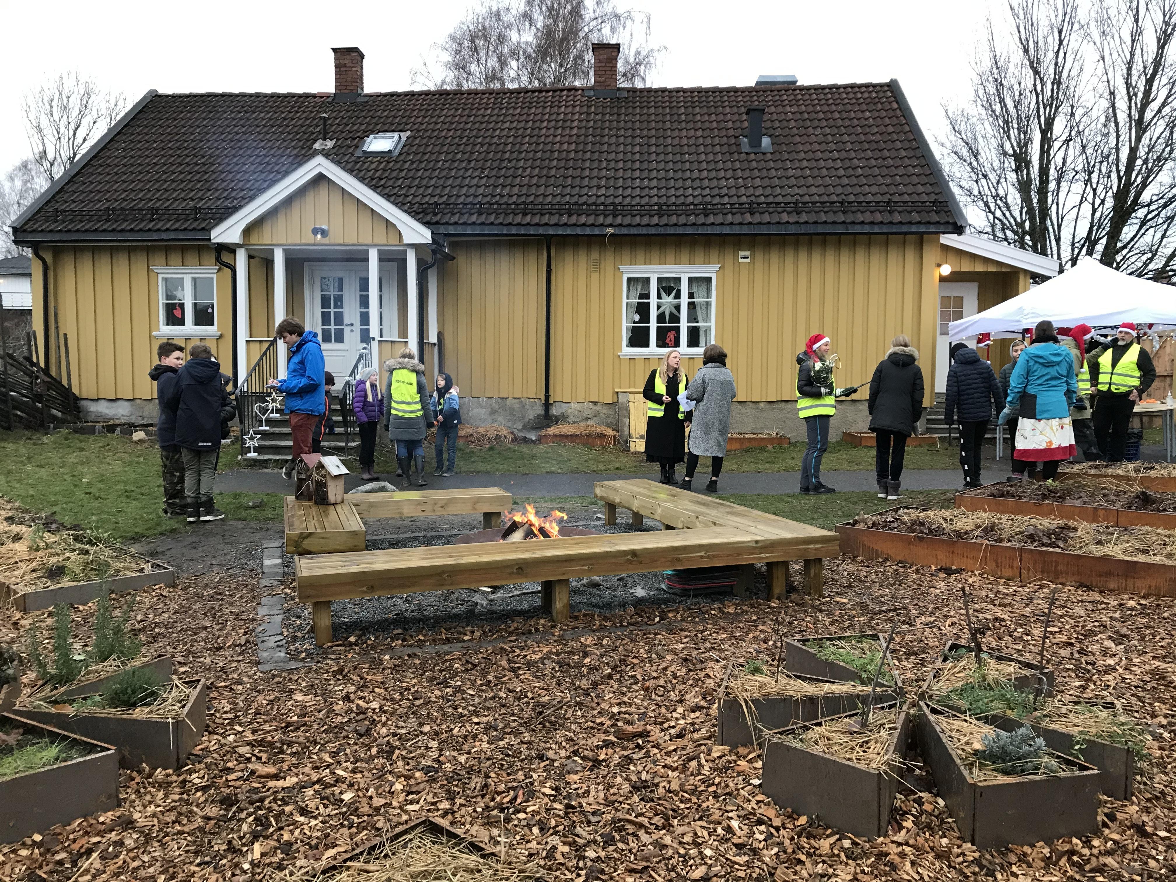 Plantekasser med krydderurter i forgrunnen. Skolehagen har også blitt et viktig samlingssted, med en koselig bålplass.