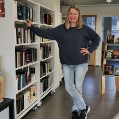 Stine Andrea Heggen mellom  bokhyllene på biblioteket i Brandbu.