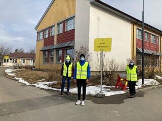 Foto av tre frivillige parkeringsvakter utenfor koronasenteret