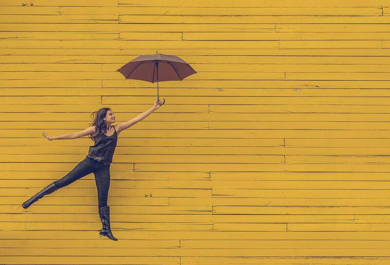 Dame med paraply mot gul vegg