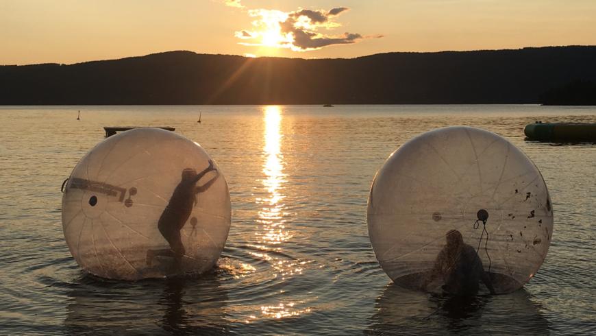 Bilde av to personer som er inne i zorb-baller på vannet.